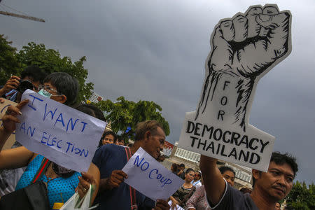 Demonstrators hold up signs during a protest against military rule at Victory Monument in Bangkok
