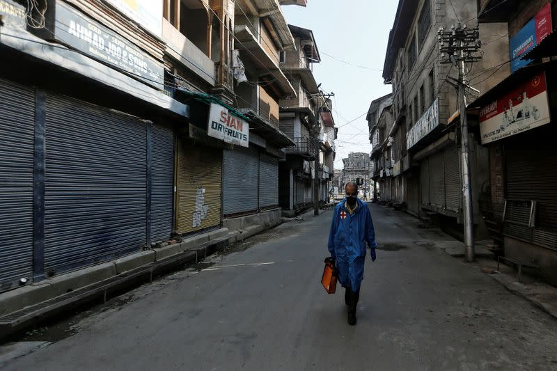 Paramedic walks through a deserted street during curfew ahead of the first anniversary of the revocation of Kashmir's autonomy in Srinagar