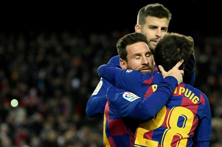 Lionel Messi (L) is congratulated by Riqui Puig after scoring Barcelona's winning goal against Granada (AFP Photo/LLUIS GENE)