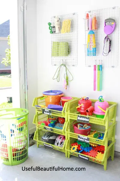 """<p>Stackable plastic baskets are easily cleaned, making them the perfect system for stashing away grimy outdoor toys in the garage. Just be sure to them low to the ground and lidless, so little ones can get into them.</p><p><strong>Get the tutorial at <a href=""""https://orgjunkie.com/2013/05/organizing-concepts-for-kids-garage-toys-free-printable.html"""" rel=""""nofollow noopener"""" target=""""_blank"""" data-ylk=""""slk:Organizing Junkie"""" class=""""link rapid-noclick-resp"""">Organizing Junkie</a>.</strong></p><p><strong><a class=""""link rapid-noclick-resp"""" href=""""https://www.amazon.com/Jumbo-Stacking-Basket-Pack-White/dp/B00GLQX4RI/ref=as_li_ss_tl?tag=syn-yahoo-20&ascsubtag=%5Bartid%7C10050.g.36449426%5Bsrc%7Cyahoo-us"""" rel=""""nofollow noopener"""" target=""""_blank"""" data-ylk=""""slk:SHOP PLASTIC BASKETS"""">SHOP PLASTIC BASKETS</a></strong></p>"""