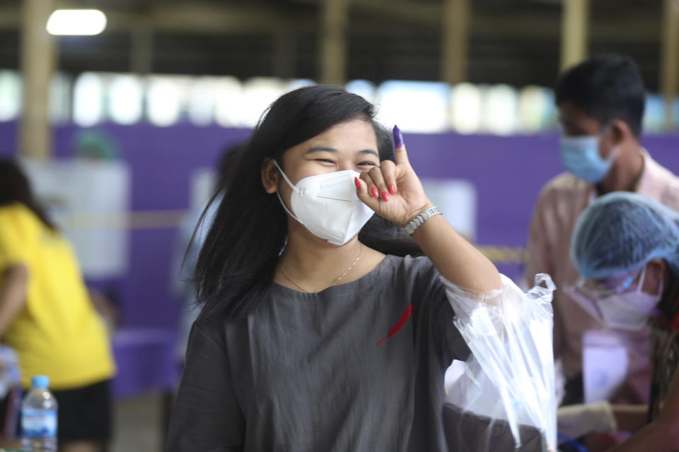 A voter wearing protective face mask shows off her finger marked with ink indicating she voted as she leaves a polling station Sunday, Nov. 8, 2020, in Yangon, Myanmar. Voting was underway in Myanmar's elections on Sunday, with the party of Nobel Peace Prize laureate Aung San Suu Kyi heavily favored to retain power it had wrestled from the powerful military five years ago. (AP Photo/Thein Zaw)