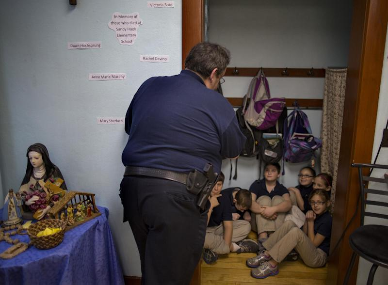 FILE - In this file photo of Jan. 14, 2013, New Washington, Ohio, Chief of Police Scott Robertson talks with fourth grade students as they huddle in closet a during a lockdown drill at the St. Bernard School in New Washington, Ohio, a month after the Sandy Hook Elementary School massacre in Newtown, Conn., that killed 26 people in December. Inspired by the memories of those who lost their lives, St. Bernard School's principal decided to hold lockdown drills on the 14th of each month to refine a safety plan and increase school security. (AP Photo/Craig Ruttle, File)