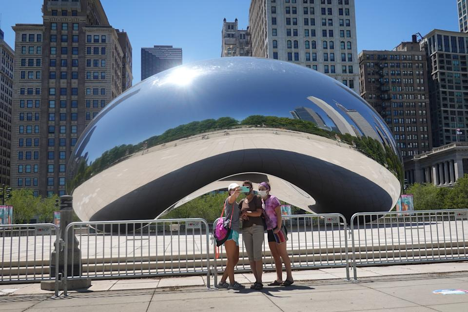 CHICAGO, ILLINOIS - JUNE 15: Visitors take pictures in front of the Cloud Gate sculpture in Millennium Park on June 15, 2020 in Chicago, Illinois. The park, which had been closed to visitors to help curtail the spread of the coronavirus COVID-19, partially reopened, with restrictions, to the public today. The park located in downtown Chicago is the most visited tourist attraction in the Midwest, attracting more than 12 million visitors annually. (Photo by Scott Olson/Getty Images)