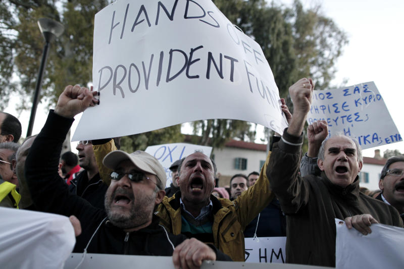 """Bank employees protest outside the ministry of finance on Saturday, March 23, 2013. Thousands of bank employees took part in a protest that ended outside the Cypriot parliament. Politicians in Cyprus were racing Saturday to complete an alternative plan raising funds necessary for the country to qualify for an international bailout, with a potential bankruptcy just three days away. Banner at right reads: """"Who voted for you members of parliament? The Troika?"""" (AP Photo/Petros Giannakouris)"""