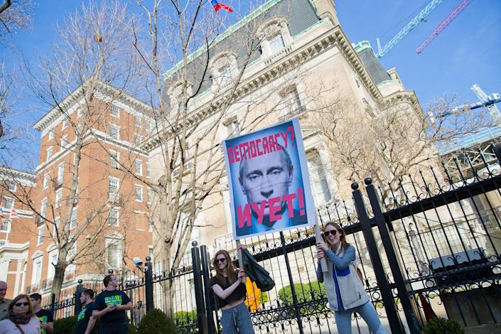 <p>A pair of demonstrators hold up a sign showing Russian President Vladimir Putin in front of the Russian ambassador's residence in downtown Washington, D.C., during a march to the White House during a 'Not My President's Day' rally, Feb. 20, 2017. Anti-Trump activists seized on Monday's federal holiday to organize rallies in cities around the country. (AP Photo/Pablo Martinez Monsivais) </p>