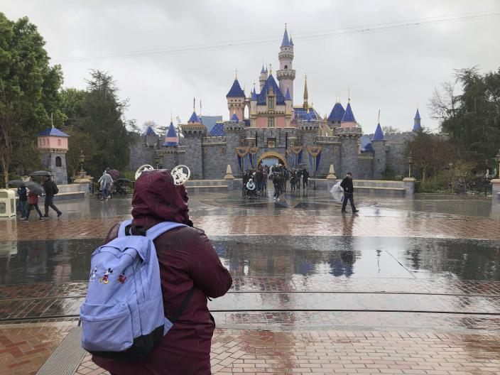 A visitor stands in the rain at Disneyland in Anaheim, Calif., Friday, March 13, 2020. Disneyland is closing its doors for the rest of the month, shuttering one of California's best-known attractions as the state hurries to stop the spread of the coronavirus. (AP Photo/Amy Taxin)