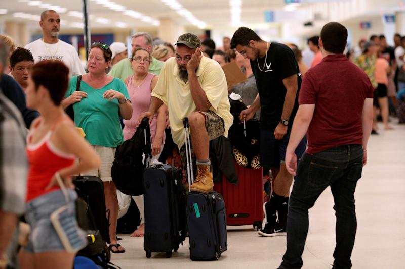 Stranded tourists and Puerto Ricans line up at the International Airport in San Juan on Sept. 25 as they try to leave after Hurricane Maria devastated power and communications across the island.