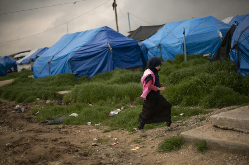 In this March 27, 2019 photo, a girl walks through a tented area at Roj camp, where families of Islamic State supporters are held, near Derik, Syria. The IS could get a new injection of life if conflict erupts between the Kurds and Turkey in northeast Syria as the U.S. pulls its troops back from the area. The White House has said Turkey will take over responsibility for the thousands of IS fighters captured during the long campaign that defeated the militants in Syria. But it's not clear how that could happen. (AP Photo/Maya Alleruzzo)