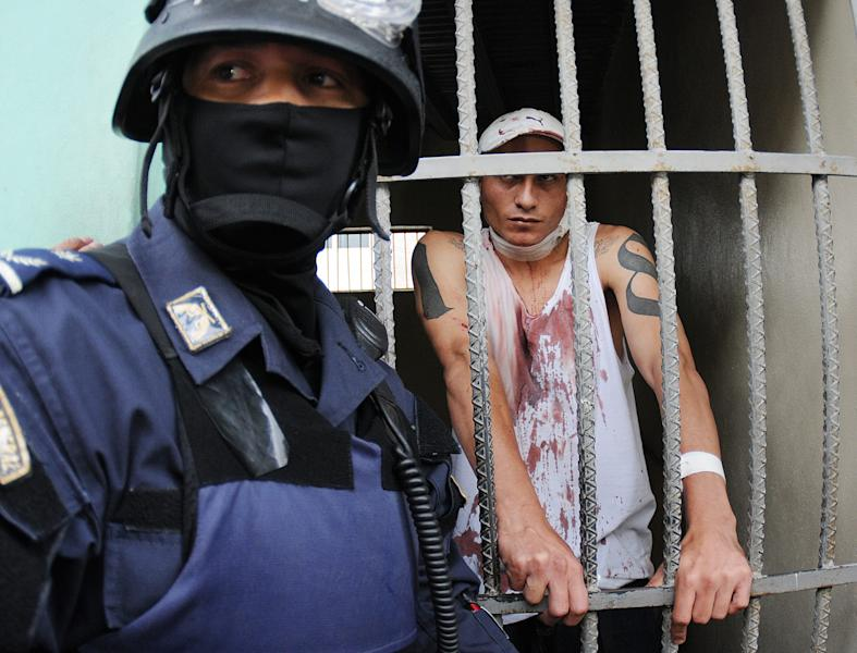 A Honduran police officer guards an injured prisoner, standing inside a cell at the Hospital Escuela, in Tegucigalpa, Honduras, Saturday, Aug. 3, 2013.Honduran President Porfirio Lobo ordered the militarization of the country's main prison on Saturday after a riot there left at least three gang members dead and three guards injured. Police said members of the 18 gang clashed with common criminals in Honduras' National Penitentiary, located 10 miles (15 kilometers) north of the capital. (AP Photo/Fernando Antonio)