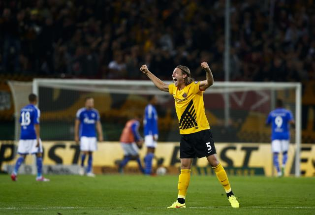 Dynamo Dresden's Michael Hefele celebrates after his team scored against Schalke 04 during their German soccer cup (DFB Pokal) match in Dresden August 18, 2014. REUTERS/Thomas Peter (GERMANY - Tags: SPORT SOCCER) DFB RULES PROHIBIT USE IN MMS SERVICES VIA HANDHELD DEVICES UNTIL TWO HOURS AFTER A MATCH AND ANY USAGE ON INTERNET OR ONLINE MEDIA SIMULATING VIDEO FOOTAGE DURING THE MATCH