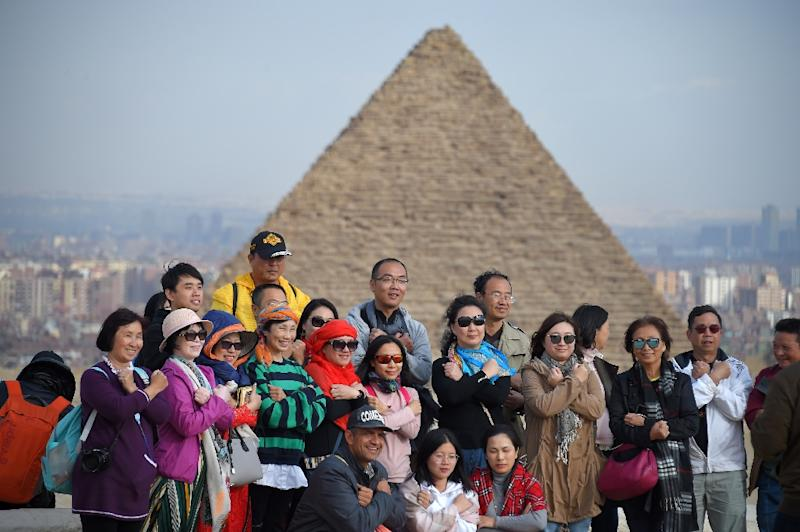 Tourists pose for a group picture at the Giza pyramids on the southwestern outskirts of the Egyptian capital Cairo on December 29, 2018 (AFP Photo/MOHAMED EL-SHAHED                   )