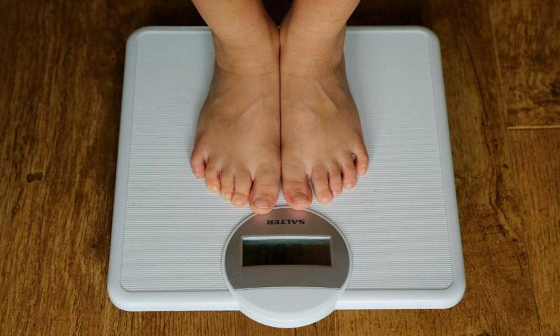 The feet of a person being weighed on scales