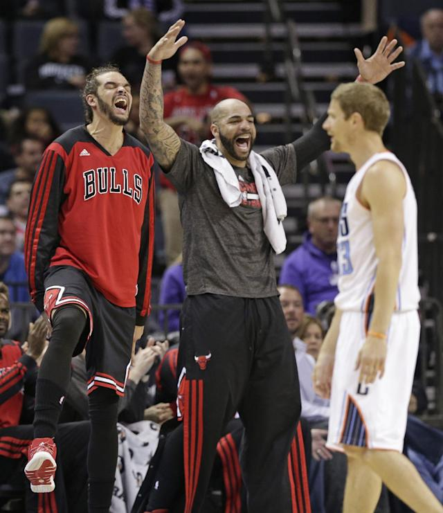 Chicago Bulls' Joakim Noah, left, and Carlos Boozer, center, react after Charlotte Bobcats' Luke Ridnour, right, was called for a foul during the first half of an NBA basketball game in Charlotte, N.C., Wednesday, April 16, 2014. (AP Photo/Chuck Burton)