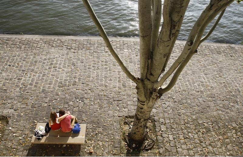 This Oct. 23, 2012 photo shows a couple sitting in the sun on the Seine river bank in Paris. Couples are often found kissing on park benches, street corners, or walking wistfully hand in hand along the banks of the tranquil river Seine.  (AP Photo/Remy de la Mauviniere)