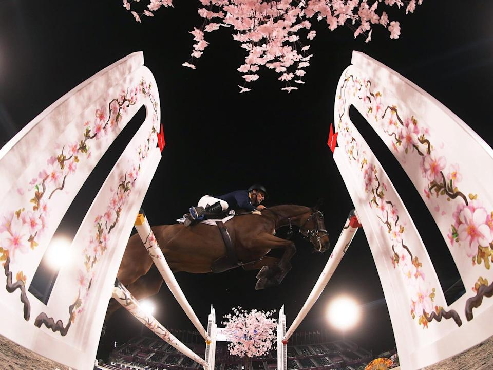 A horse jumps over bars at the Tokyo Olympics