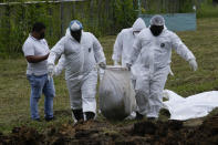 A forensics team bury a group of 15 migrants who died trying to cross the Darien Gap, at the Guayabillo cemetery in Agua Fria, Panama, Thursday, Sept. 30, 2021. The migrants, who are buried with plasticized cards containing what little information investigators were able to gather, die of natural causes or in accidental deaths while crossing the Darien jungle trying to make their way to the United States. (AP Photo/Arnulfo Franco)