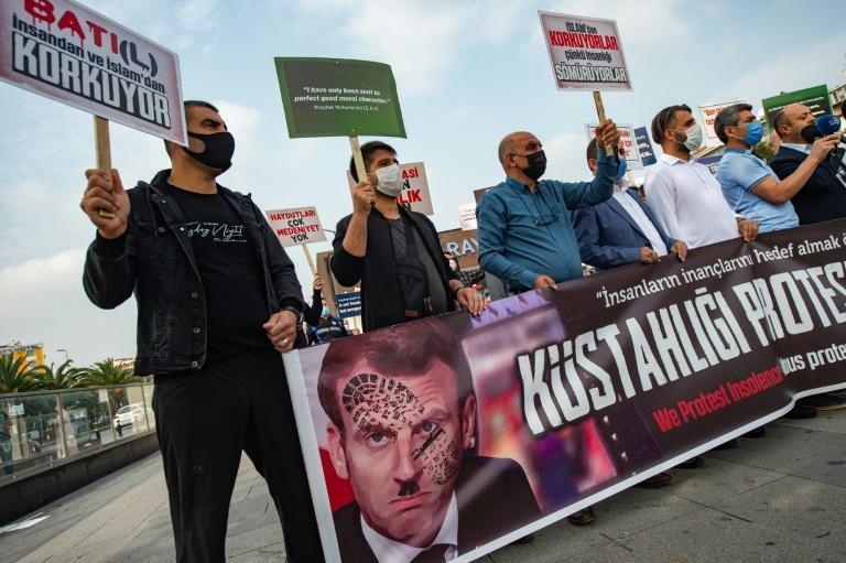 Protesters in Istanbul hold a sign showing French President Emmanuel Macron with a shoe print over his face after he defended the right to mock religion following the beheading of a teacher near Paris who had shown cartoons of the Prophet Mohammed
