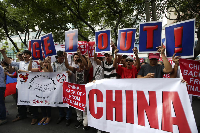 FILE - In this May 16, 2014, file photo, Vietnamese expatriates and Filipinos protest the recent moves by China to construct an oil rig near the Vietnamese-claimed Paracels off the contested Spratlys group of islands and shoals in the South China Sea. In comments last week, Vietnamese President Nguyen Phu Trong said it was time to take stock after three months of tensions with Beijing over Vietnamese-controlled Vanguard Reef that China also claims, according to Hong Kong's South China Morning Post news. (AP Photo/Bullit Marquez, File)