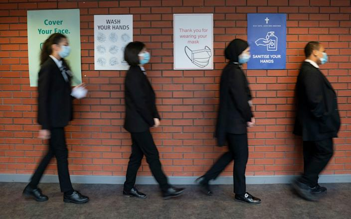 Pupils queue for a socially distanced assembly at a school in in Manchester - Jon Super/AP