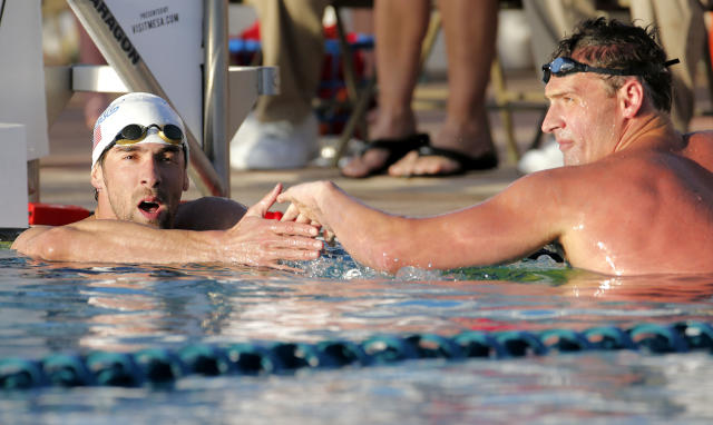 Michael Phelps, left, congratulates Ryan Lochte on Lochte's win in the 100-meter butterfly final during the Arena Grand Prix, Thursday, April 24, 2014, in Mesa, Ariz. Phelps was competing for the first time since the 2012 London Olympics. (AP Photo/Matt York)