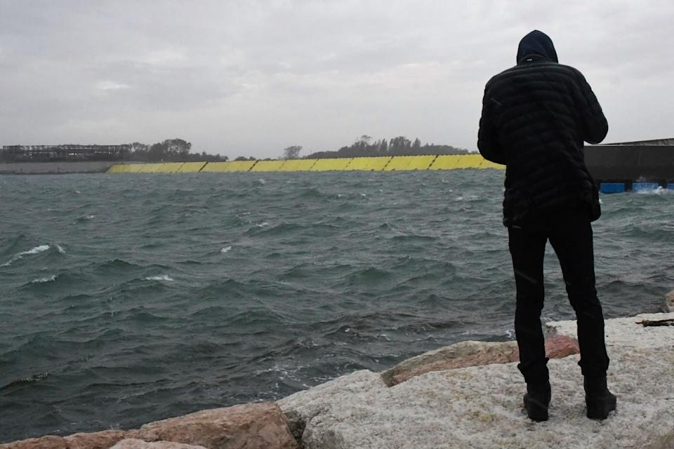 "A man stands on dam near the mobile gates of the MOSE Experimental Electromechanical Module (Rear in yellow) that protects the city of Venice from floods, at the Malamocco inlet off Venice's Lido on October 3, 2020 during a high tide ""Alta Acqua"" phenomenon, following a peak of water following bad weather and potential intense sirocco winds along the entire Adriatic basin. - Together with other measures, such as coastal reinforcement, the raising of quaysides, and the paving and improvement of the lagoon, MOSE is designed to protect Venice and the lagoon from tides of up to 3 metres. (Photo by ANDREA PATTARO / AFP) (Photo by ANDREA PATTARO/AFP via Getty Images) (Photo: ANDREA PATTARO via Getty Images)"