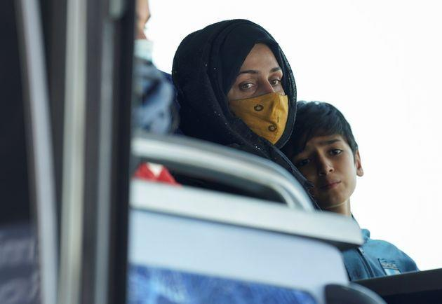 An Afghan woman and boy sit on a bus taking them to a refugee processing center upon arrival at Dulles International Airport in Dulles, Virginia, U.S., August 24, 2021. REUTERS/Kevin Lamarque (Photo: Kevin Lamarque via Reuters)