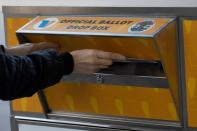 A person drops a ballot into an Official Los Angeles County Ballot Drop Box during the U.S. presidential election outside Hollywood Bowl during the outbreak of the coronavirus disease (COVID-19), in Los Angeles