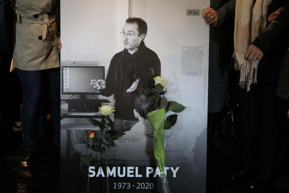 People hold a photo of the history teacher Samuel Paty , who was beheaded last week, during a memorial march in homage to him, Tuesday, Oct.20, 2020 in Conflans-Sainte-Honorine, northwest of Paris. Samuel Paty was beheaded on Friday by an 18-year-old Moscow-born Chechen refugee, who was later shot dead by police. Police officials said Paty had discussed caricatures of Islam's Prophet Muhammad with his class, leading to threats. (AP Photo/Lewis Joly)