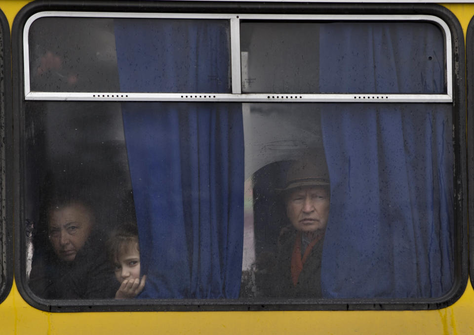 """FILE - In this Friday, March 7, 2014 file photo, people in a passing bus watch a rally against the breakup of the country in Simferopol, Ukraine. Despite the pebble beaches and cliff-hung castles that made Ukraine's region of Crimea famous as a Soviet resort hub, the peninsula has long been a corruption-riddled backwater in economic terms. The Kremlin, which has moved to annex the region after its residents voted in a referendum on Sunday to join Russia, has begun calculating exactly what it will cost to support the region's shambolic economy - which one Russian minister described as """"no better than Palestine."""" (AP Photo/Vadim Ghirda, File)"""
