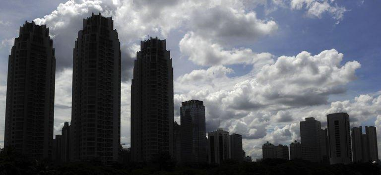 High rise buildings stand against a backdrop of clouds in Jakarta on December 27, 2012