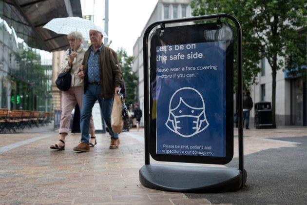 Shoppers pass a sign encouraging people to wear masks to reduce the transmission of the coronavirus outside of a Tesco supermarket. The U.K. has the second highest number of COVID-19 cases, according to the WHO. (Photo: Daniel Harvey Gonzalez via Getty Images)