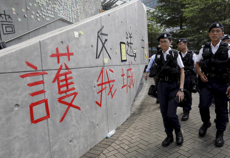 "Hong Kong police officers pass by words formed with tape which read ""Protect our city, against extradition to China"" near the Legislative Council in Hong Kong on Friday, June 14, 2019. Calm appeared to have returned to Hong Kong after days of protests by students and human rights activists opposed to a bill that would allow suspects to be tried in mainland Chinese courts. (AP Photo/Vincent Yu)"