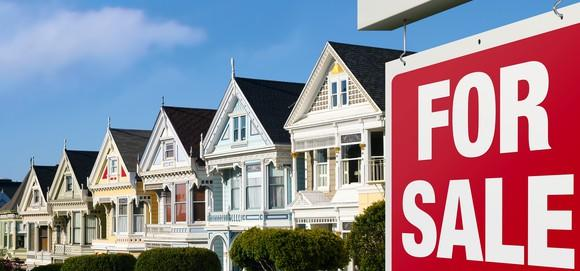 A row of Victorian houses and a For Sale sign in San Francisco.