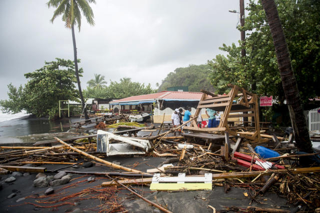 <p>People stand next to debris at a restaurant in Le Carbet, on the French Caribbean island of Martinique, after it was hit by Hurricane Maria, on Sept. 19, 2017. (Photo: Lionel Chamoiseau/AFP/Getty Images) </p>