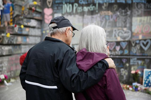 <p>Mark Landa, 72, and Mary Brooks, 68, of Portland, pay their respects at a makeshift memorial for two men who were killed on a commuter train while trying to stop another man from harassing two young women who appeared to be Muslim, in Portland, Ore., May 29, 2017. (Terray Sylvester/Reuters) </p>