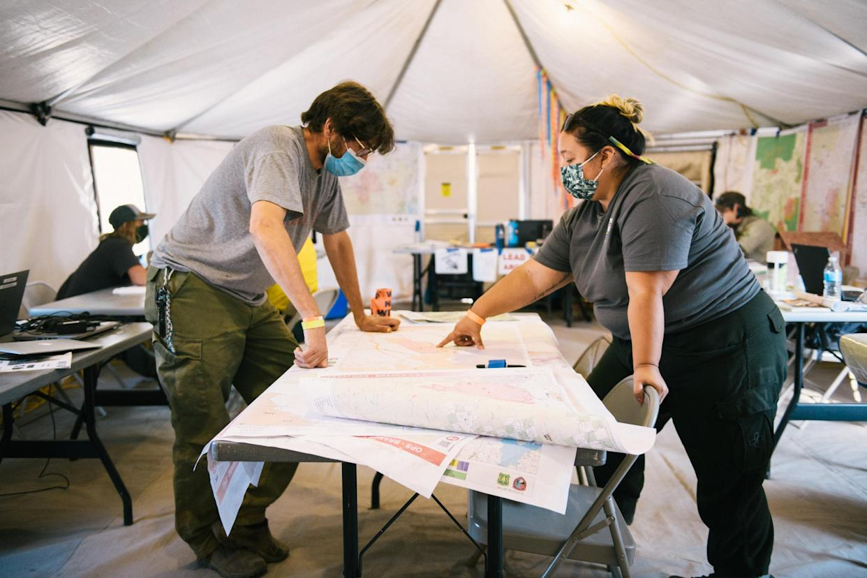 Vikki Preston, the Karuk tribal government representative on the Cronan Fire, and tribal fire line resource adviser Alex Watts-Tobinlook at a map at the fire camp in Etna, Calif. (Alexandra Hootnick for Yahoo News)