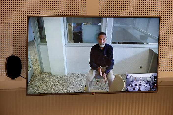 John McAfee, creator of McAfee antivirus software is seen on a screen while testifying via video during an extradition hearing at the National Court in Madrid, Spain, on June 15, 2021. McAfee has been found dead on Wednesday June 24, 2021, in his jail cell near Barcelona in an apparent suicide, hours after a Spanish court approved his extradition to the United States to face tax charges which may have been punishable by decades in prison. Inset photo bottom right is a view of the courtroom. (Chema Moya, Pool photo via AP)