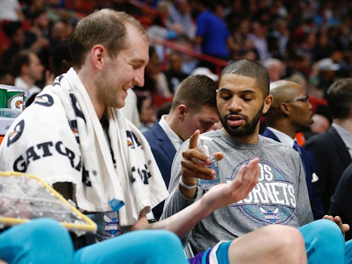 The Charlotte Hornets' Nic Batum gives Cody Zeller hand sanitizer on the bench.