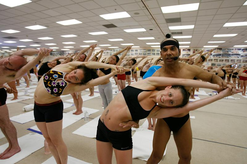 Jeanne Orzano is adjusted by Bikram Choudhury during a class in 2006.