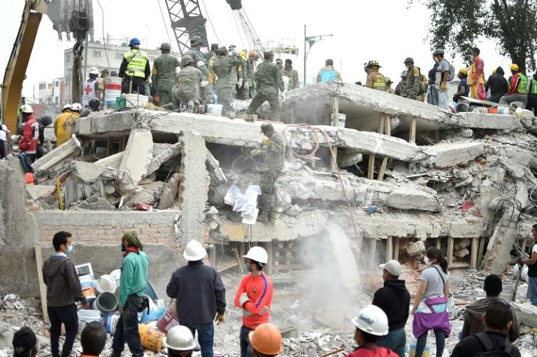 Rescuers clear rubble and debris from the site where a multistory building was flattened by the 7.1-magnitude quake