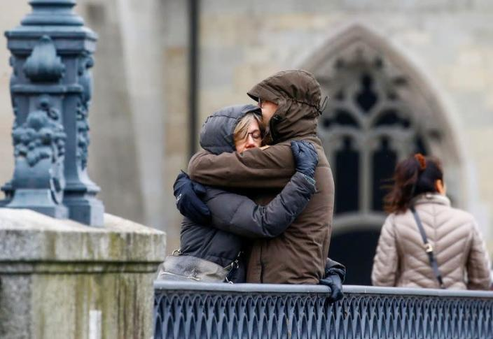 People hug each other as the bells of all churches ring to commemorate Swiss victims of COVID-19 in Zurich