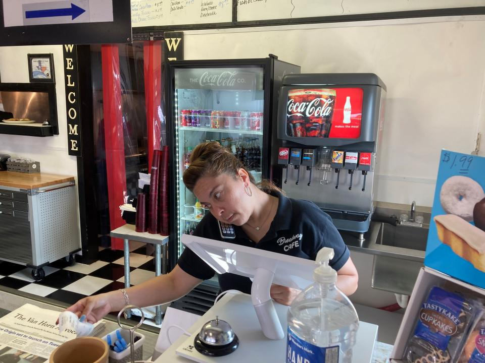 Valentina Muro rings up a customer at the Broadway Café in Van Horn, Texas, on Sunday, July 18, 2021, just days before Blue Origin plans to launch a manned spacecraft from its spaceport about 25 miles outside of the West Texas town. (AP Photo/Sean Murphy)