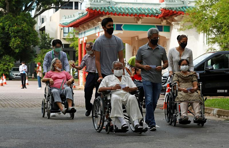 Wheelchair-bound voters arrive at a polling station at a time band allocated to seniors and elders as part of preventive measures against the coronavirus disease (COVID-19) outbreak, during the general election in Singapore July 10, 2020. REUTERS/Edgar Su