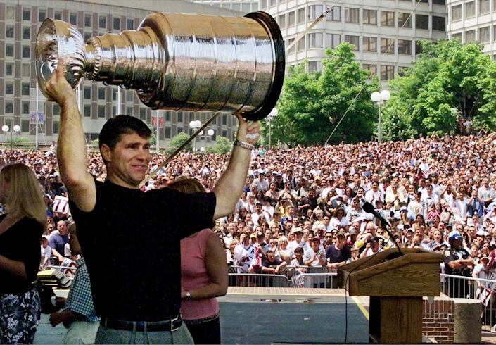Longtime Boston Bruin Ray Bourque hoists the Stanley Cup in front of a crowd of more than 10,000 cheering Bostonians on City Hall Plaza on June 13, 2001 after his team, the Colorado Avalanche, won the championship. (JRB/RCS/Reuters)