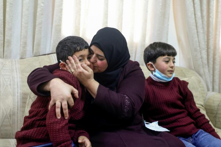 Dalal Zibn poses with her children Salaheddine and Muhannad, conceived via IVF, as their father is detained in Israel