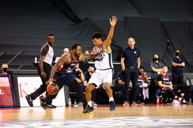 Niagara's Trae Bell-Haynes, right, defends against Ottawa's Junior Cadougan during a 2020 CEBL game. While Cadougan has suited up for Team Canada as recently as 2017, Bell-Haynes' inclusion in the pre-Olympic qualifier training camp shows how the league can benefit Canada Basketball and vice versa. (CEBL - image credit)