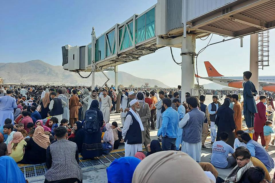Afghans crowd at the tarmac of the Kabul airport on August 16, 2021, to flee the country as the Taliban were in control of Afghanistan after President Ashraf Ghani fled the country and conceded the insurgents had won the 20-year war. (Photo by - / AFP) (Photo by -/AFP via Getty Images)