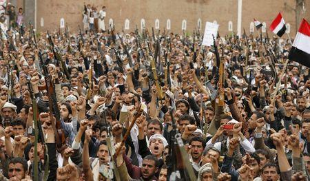 Shi'ite Muslim rebels hold up their weapons during a rally against air strikes in Sanaa March 26, 2015. REUTERS/Khaled Abdullah