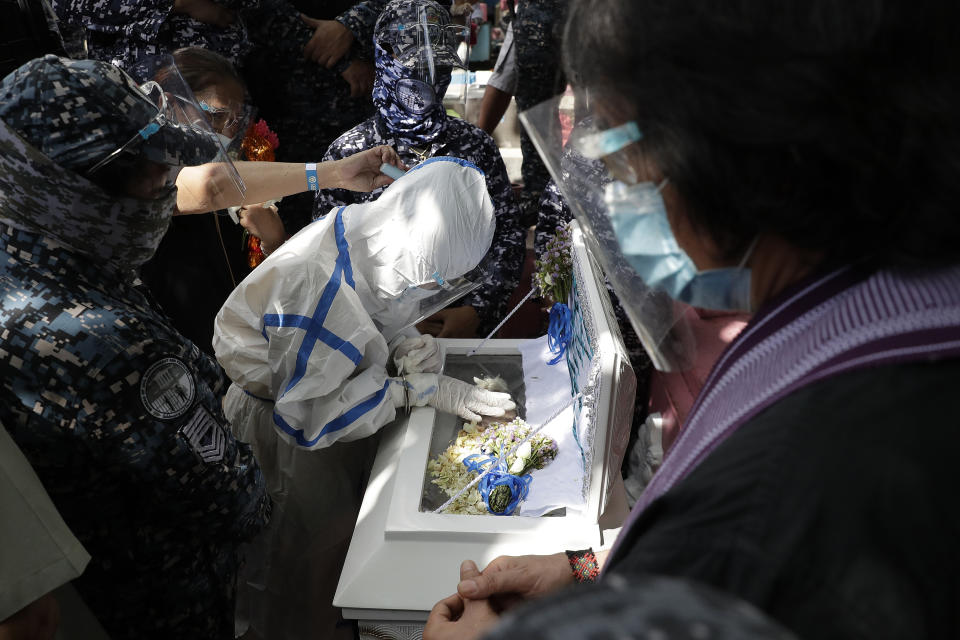 Detained left-wing activist Reina Mae Nasino in handcuffs and wearing protective suit to prevent the spread of the coronavirus touches the coffin of her three-month-old firstborn named River during funeral rites at Manila's North Cemetery, Philippines on Friday Oct. 16, 2020. Left-wing groups on Friday decried the treatment as brutal of Nasino, who was allowed by a Manila court to attend her baby's burial but was restrained with handcuffs, a sweltering protective suit and swarms of armed escorts as she quietly wept. (AP Photo/Aaron Favila)