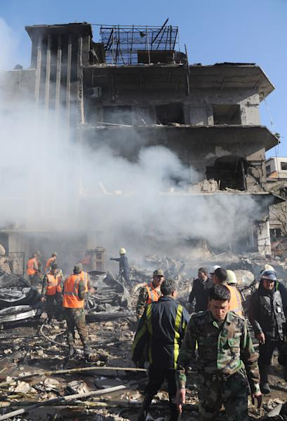 "In this photo released by the Syrian official news agency SANA, Syrian army soldiers and security officers inspect the blast area in front of a damaged building of the air intelligence forces, which was attacked by one of two explosions, in Damascus, Syria, on Saturday, March 17, 2012. Two ""terrorist explosions"" struck security targets in the Syrian capital Saturday morning, killing a number of civilians and security forces, the country's state news agency said. The report said preliminary reports indicated they blasts were caused by car bombs that hit the aviation intelligence department and the criminal security department. (AP Photo/SANA)"